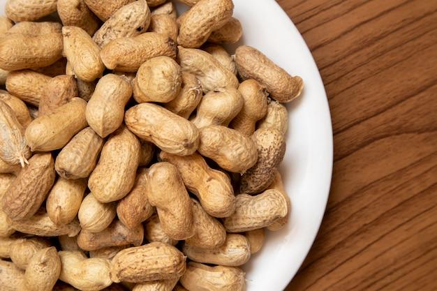 Cacahuètes grillées sur la table, recouvertes de tissu marron. Photo Premium