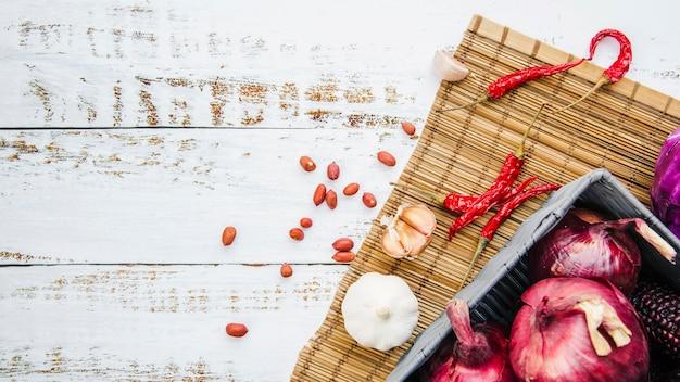 Cacahuètes; légume avec napperon sur table en bois Photo gratuit