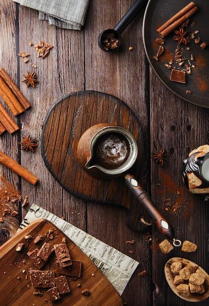 Cacao Plat Posé Sur Un Fond Rustique. Main Féminine Est Titulaire D'un Turku Avec Une Poignée En Bois De Chocolat Au Cacao Avec Une Boisson Chaude Sur Une Table En Bois, Chocolat Et Cannelle, Café De Fête Photo Premium