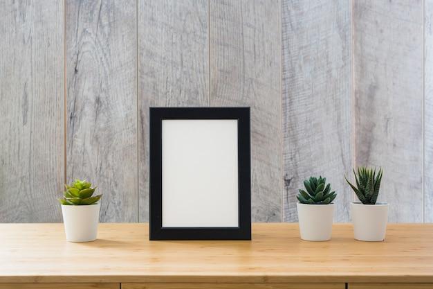 Cactus en pot et cadre photo blanc avec bordure noire sur table Photo gratuit
