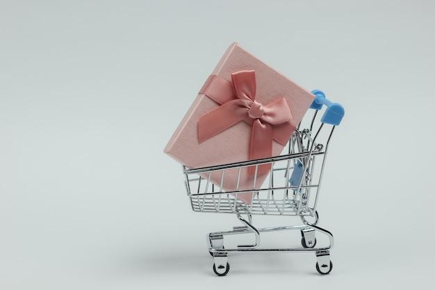 Caddie Et Boîte-cadeau Avec Noeud Sur Fond Blanc. Composition Pour Noël, Anniversaire Ou Mariage. Photo Premium