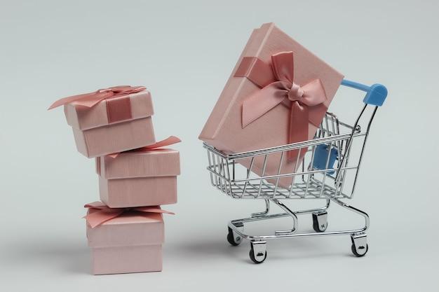 Caddie Et Coffrets Cadeaux Avec Des Arcs Sur Fond Blanc. Composition Pour Noël, Anniversaire Ou Mariage. Photo Premium