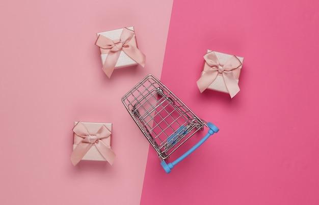 Caddie Et Coffrets Cadeaux Avec Des Arcs Sur Fond Pastel Rose. Composition Pour Noël, Anniversaire Ou Mariage. Vue De Dessus Photo Premium