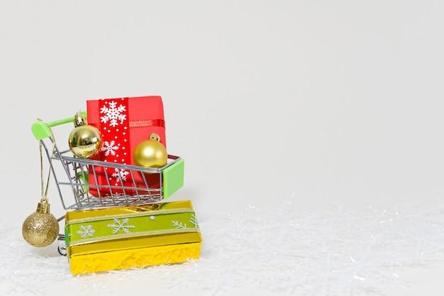 Caddie Avec Coffrets Cadeaux Et Sphères Dorées Sur Un Flocon De Neige Sur Fond Blanc Photo gratuit