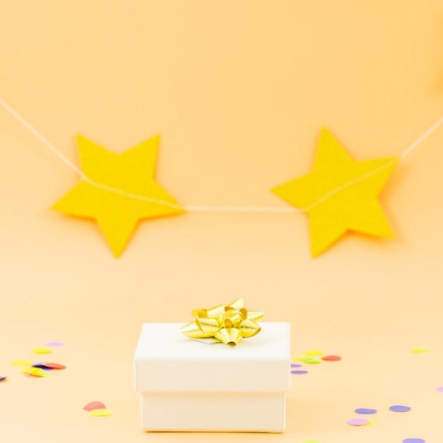 Cadeau d'anniversaire avec étoiles et confettis Photo gratuit