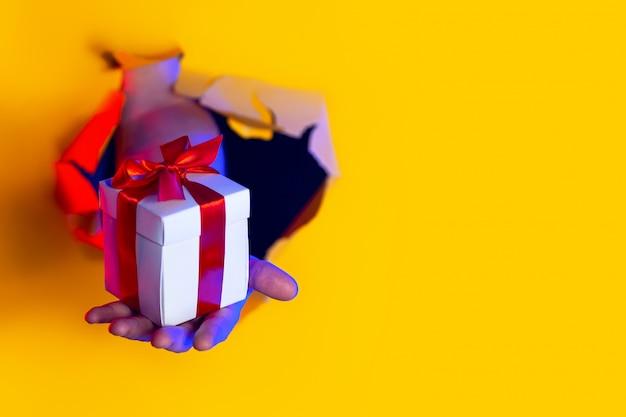 Un cadeau avec un arc rouge à la main émerge d'un trou déchiqueté sur fond de papier jaune, éclairé par une lumière au néon Photo Premium