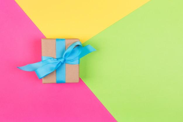 Cadeau emballé et décoré d'un arc bleu sur fond coloré avec espace de copie. Photo Premium