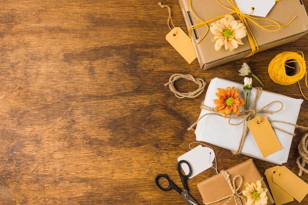 Cadeau emballé avec étiquette vide et belle fleur sur une table en bois Photo gratuit