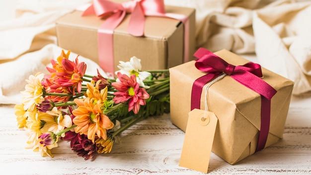 Cadeau emballé marron avec étiquette vide et beau bouquet de fleurs Photo gratuit