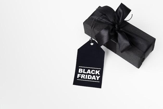 Cadeau emballé noir avec étiquette de vendredi noir Photo gratuit