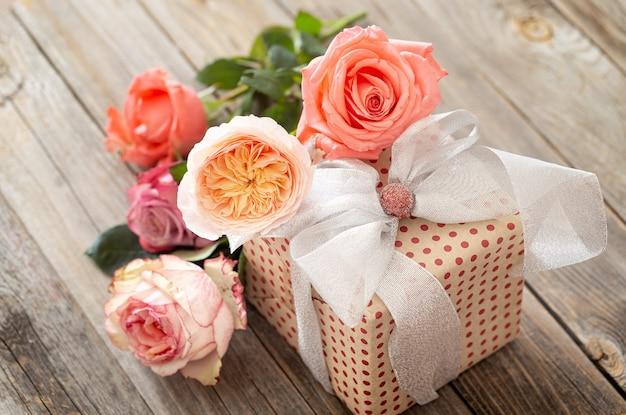 Cadeau Joliment Emballé Et Un Bouquet De Roses Sur Une Table En Bois Floue. Photo gratuit