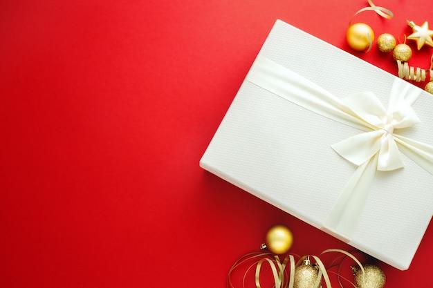 Cadeau de noël avec un arc blanc sur fond rouge Photo Premium