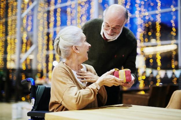 Cadeau de noël comme surprise pour femme, heureux couple de personnes âgées Photo gratuit