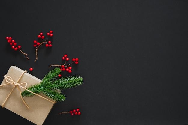 Cadeau de noël sur fond noir avec des branches de pin, des baies et de la corde Photo Premium