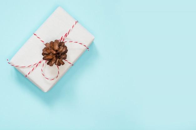 Cadeau de noël en papier blanc avec cône sur fond bleu Photo Premium