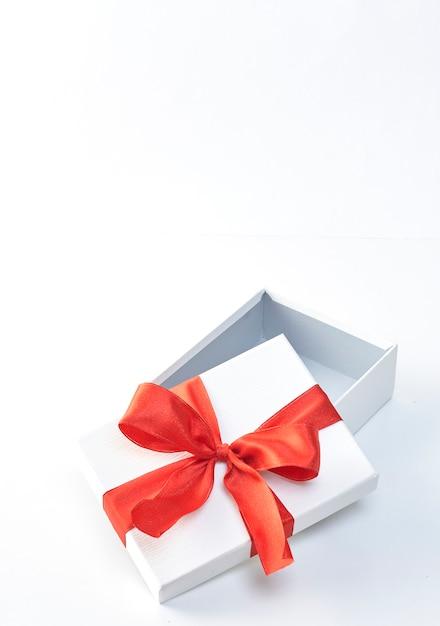 Un cadeau de noël en papier d'emballage blanc et rubans rouges Photo Premium