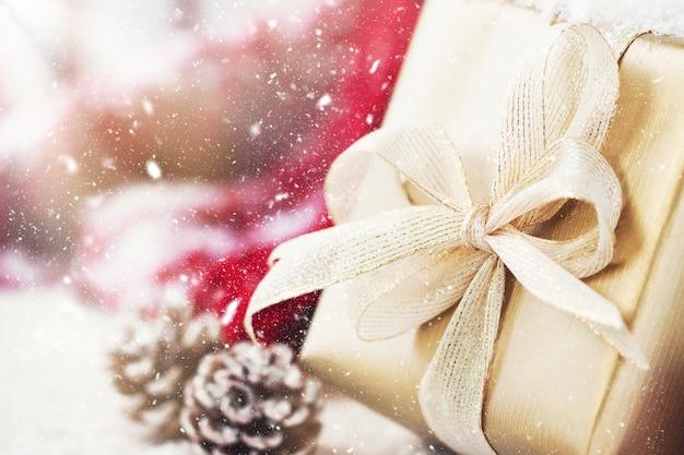 Cadeau D'or Avec Un Arc Blanc Et Pinecones Photo gratuit