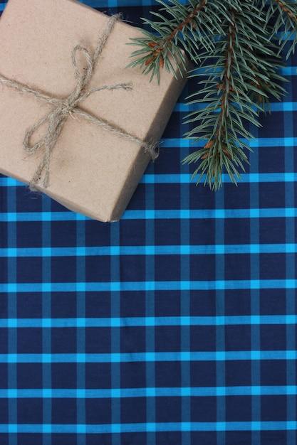 Cadeau En Papier Ordinaire Et Une Branche D'épinette Sur Fond Quadrillé Bleu, Vue Du Dessus. Texture De Vacances De Noël Ou Du Nouvel An. Pose à Plat. Copie Espace. Photo Premium