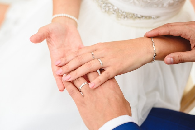 Cadeau pour la saint-valentin, les fiançailles et les alliances dans les mains des jeunes mariés. Photo Premium