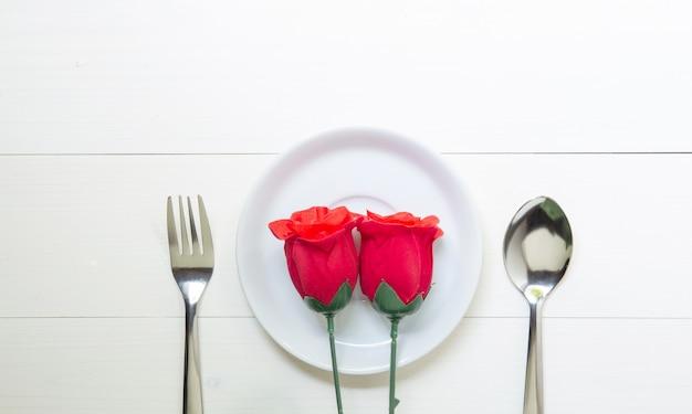Cadeau présent avec fleur rose rouge et plat et cuillère et fourchette sur table en bois Photo Premium