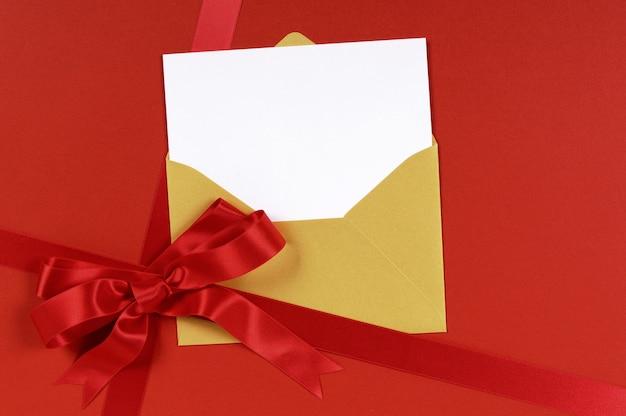 Cadeau rouge avec enveloppe d'or et invitation vierge ou carte de voeux. Photo Premium