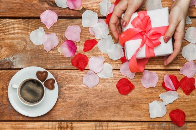 Cadeau De Saint Valentin Et Mains Féminines Sur Table En Bois Photo gratuit