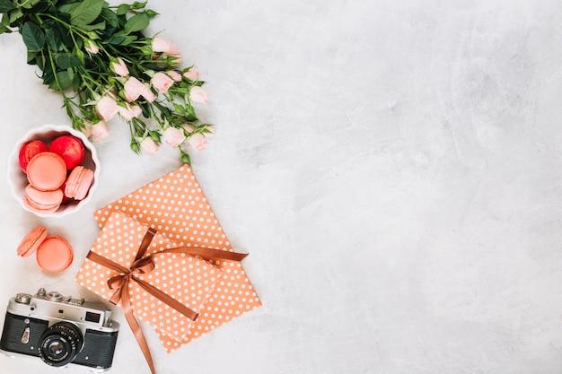 Cadeaux et appareil photo près de macarons et bouquet Photo gratuit