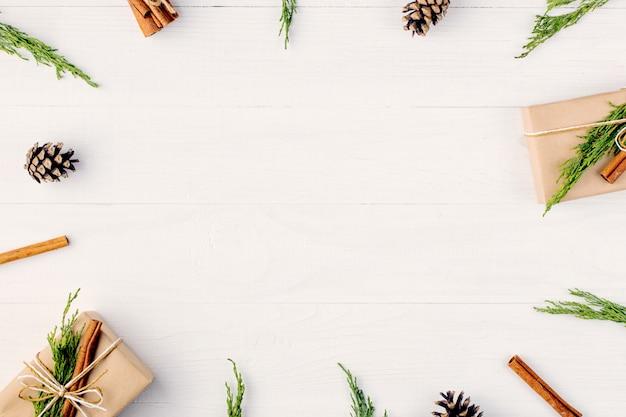 Les cadeaux et les branches de sapin forment un cadre vierge pour une carte de noël. vue de dessus. Photo Premium