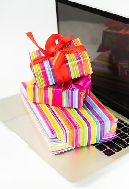 Cadeaux colorés au sommet d'un ordinateur portable Photo gratuit