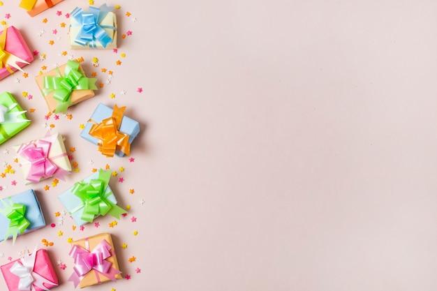 Cadeaux colorés vue de dessus sur table avec fond rose Photo gratuit