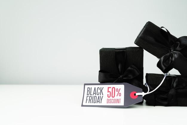 Cadeaux emballés noirs avec étiquette sur fond uni Photo gratuit