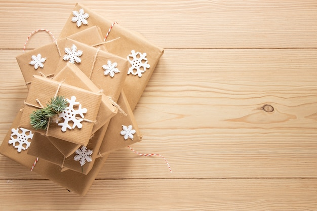 Cadeaux de fête avec des flocons de neige sur fond en bois Photo gratuit