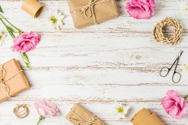 Cadeaux; fleurs et ciseaux disposés en cercle sur table Photo gratuit