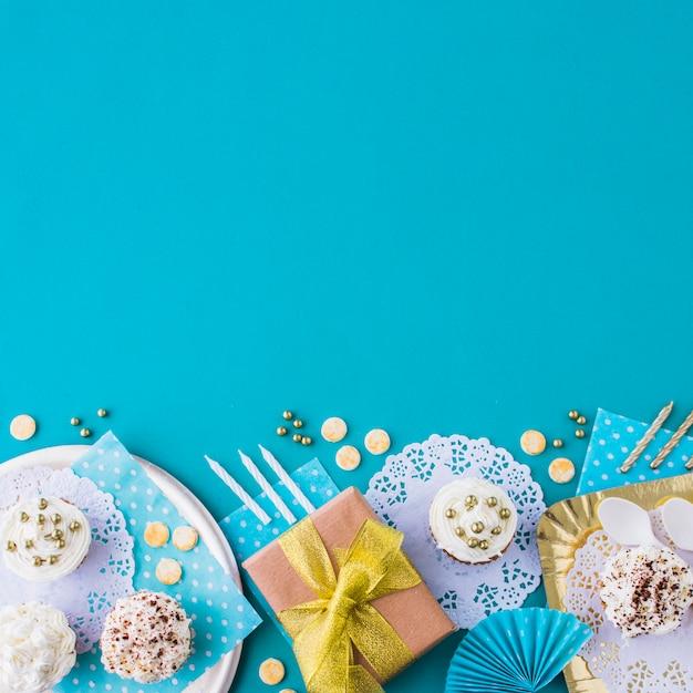 Cadeaux avec des muffins sur une assiette et un plateau au bord du fond bleu Photo gratuit