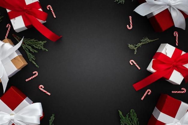 Cadeaux De Noël, Branche Pin Et Canne De Noël Sur Fond Noir Photo gratuit