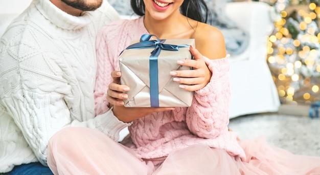 Cadeaux de noël entre les mains d'un homme et d'une femme. mise au point sélective. Photo Premium