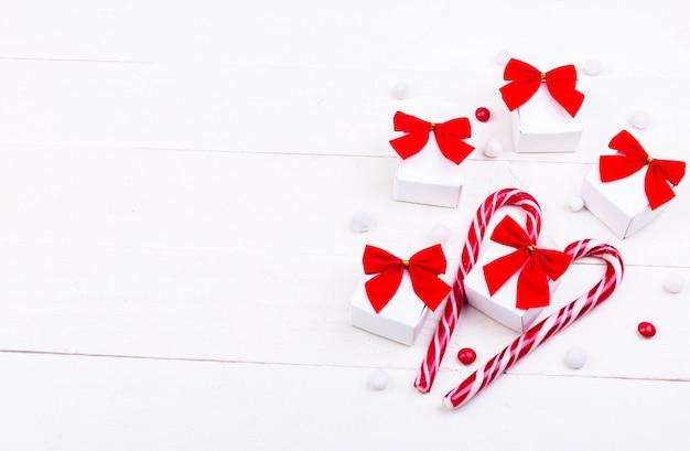 Cadeaux de noël, petites boîtes blanches avec un arc rouge et des bonbons sur un fond en bois blanc. Photo Premium
