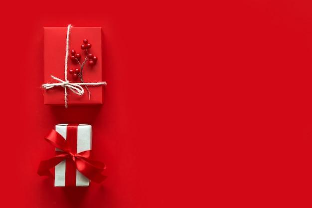 Cadeaux de noël présente sur fond rouge. coffrets cadeaux emballés simples et classiques, rouges et blancs, avec noeuds en ruban et décorations de fêtes Photo Premium