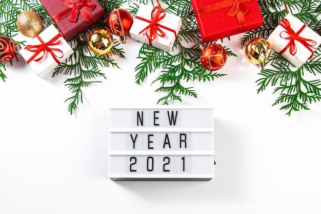 Cadeaux De Noël Avec Ruban Rouge Sur Fond Blanc. Concept Du Nouvel An 2021. Photo Premium