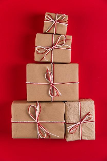 Cadeaux de papier kraft et de cordes en forme de sapin de noël sur une surface rouge, noël, de cartes de voeux. Photo Premium