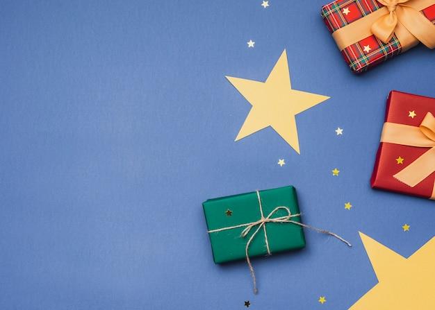 Cadeaux pour noël sur fond bleu avec des étoiles dorées Photo gratuit