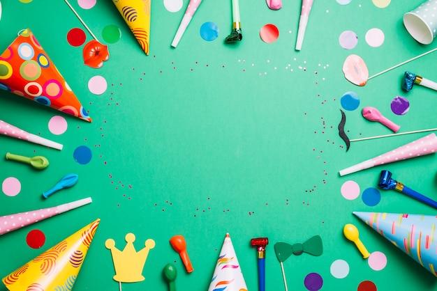 Cadre d'anniversaire coloré avec des articles de fête multicolores sur fond vert Photo gratuit