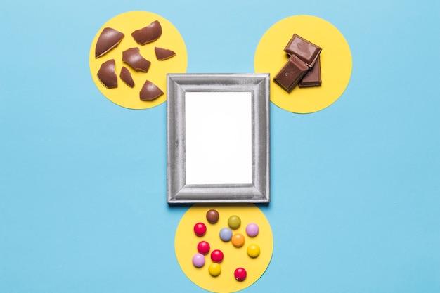 Cadre en argent blanc sur le cadre circulaire jaune avec des bonbons aux pierres précieuses; morceaux de chocolat et coquilles d'oeufs de pâques sur fond bleu Photo gratuit