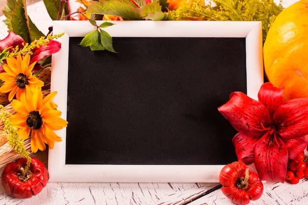 Cadre automne avec des fleurs, des légumes et des feuilles. concept de récolte, action de grâces ou chute sur fond en bois blanc. Photo Premium
