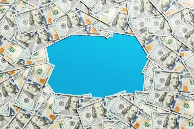 Cadre de billets de cent dollars. vue de dessus des affaires sur bleu avec fond Photo Premium