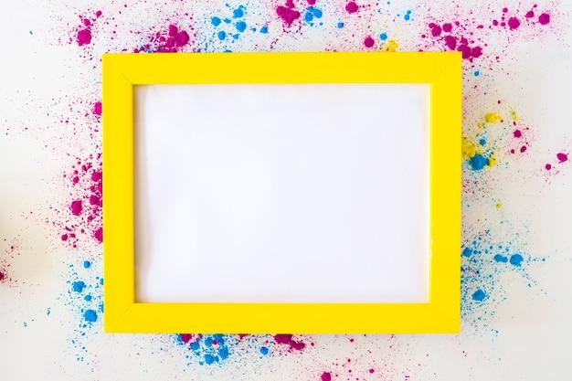 Cadre blanc blanc avec bordure jaune sur poudre de couleur holi sur fond blanc Photo gratuit