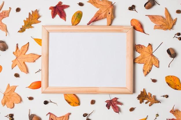 Cadre blanc en bois sur fond de feuilles d'automne Photo gratuit