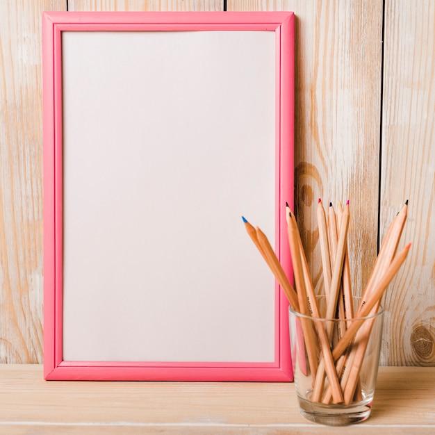 Cadre blanc avec bordure rose et crayons de couleur dans le porte-verre sur le bureau en bois Photo gratuit
