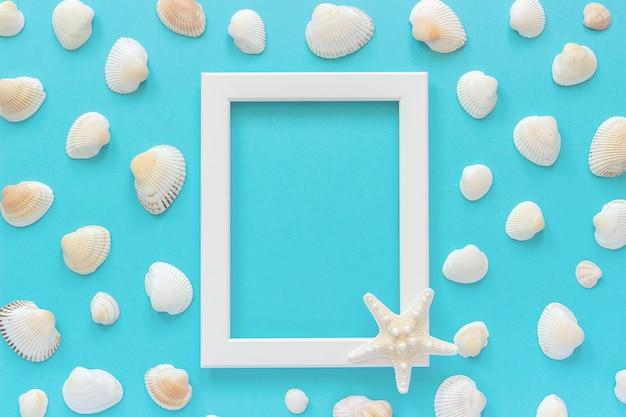 Cadre blanc avec étoile de mer sur fond bleu et coquillages Photo Premium