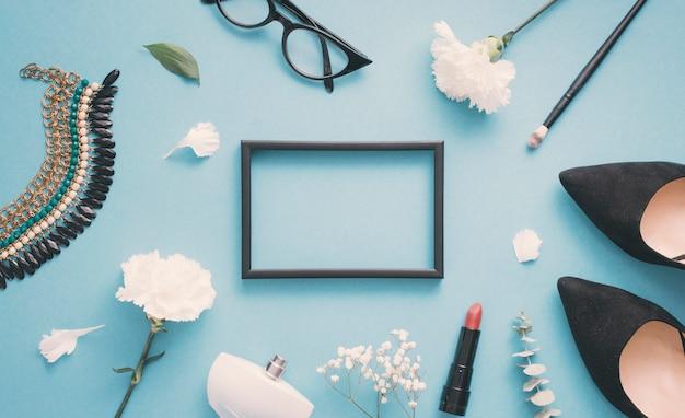 Cadre blanc avec des fleurs blanches, des chaussures de femme et des produits de beauté Photo gratuit
